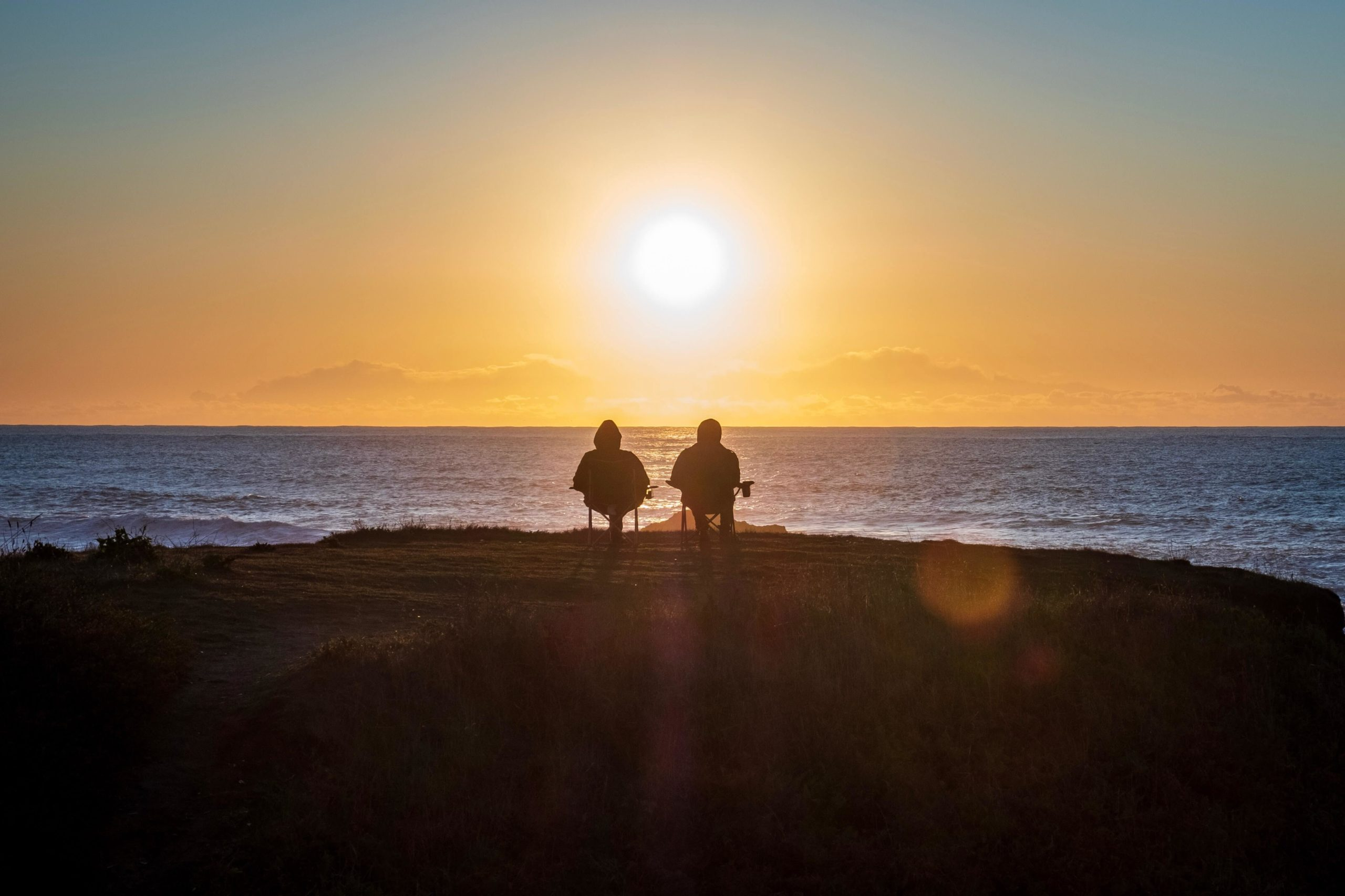 two people sitting on beach